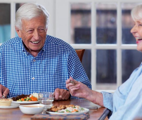 Two happy seniors sharing a meal at home