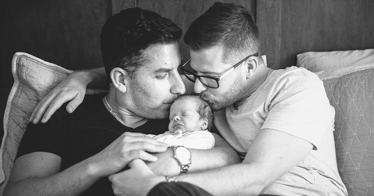 Two men kissing the head of their newborn child