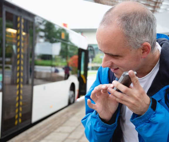 Blind man using cellphone at bus stop