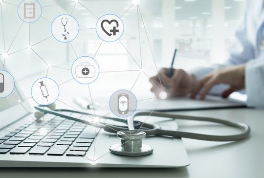 Health care icons over a doctor working with a computer
