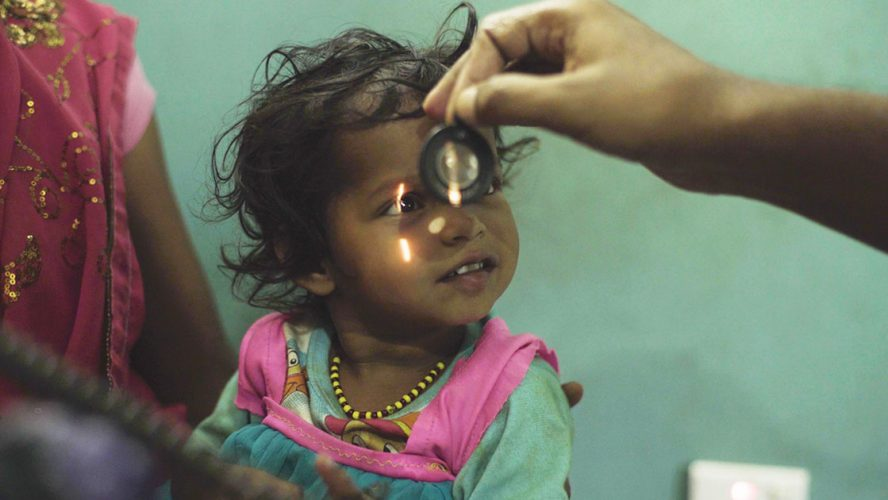 Young Nepalese girl getting her eyes checked by optometrist