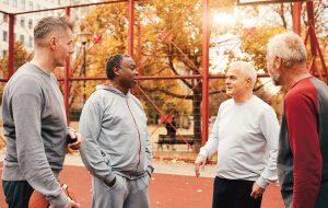 Four older men playing basketball