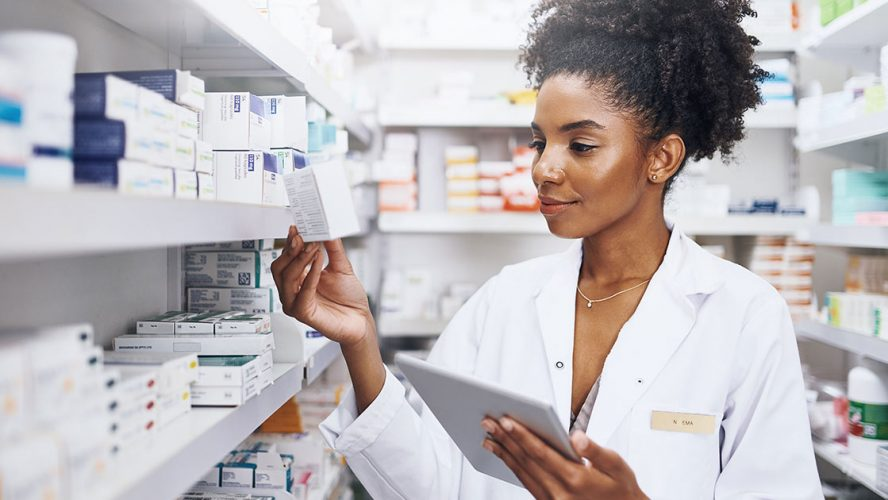 Pharmacist using tablet in the stock room