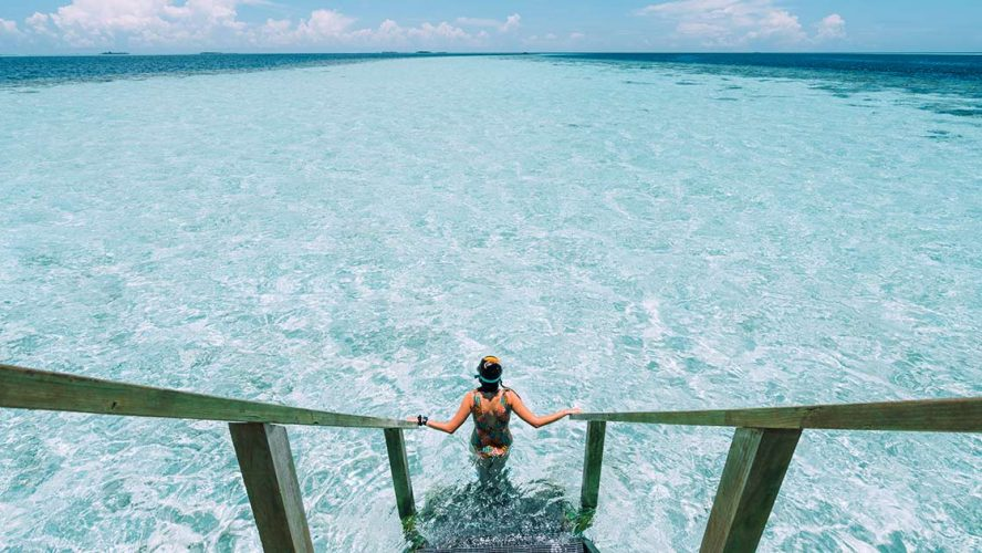 Swimmer descending into clear blue ocean