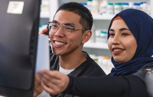 Two young pharmacy technicians working and smiling