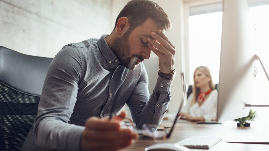 Man suffering a migraine at work