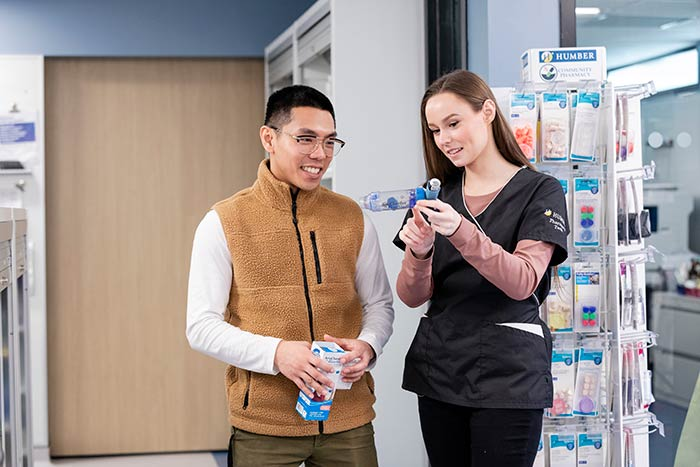 Pharmacy technician teaching patient how to use inhaler