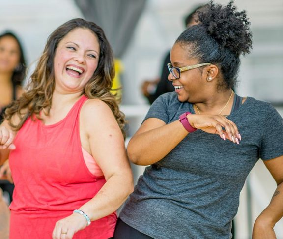 Two women dancing together at a fitness class