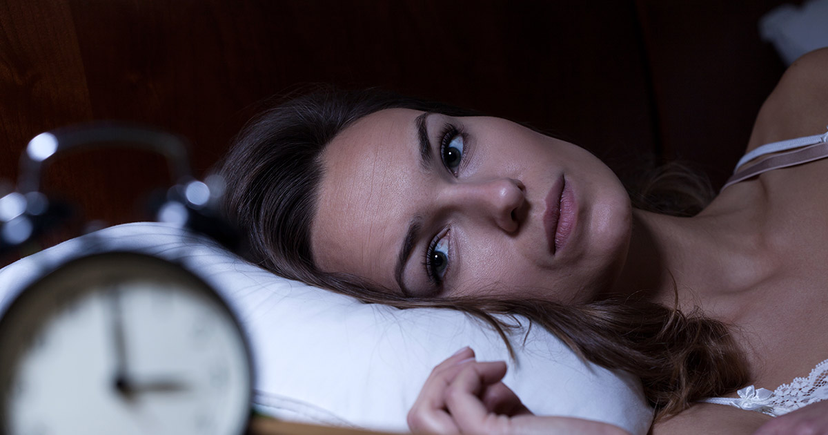 Woman staring at a clock and unable to sleep