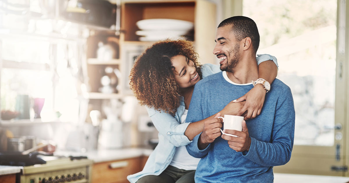 Couple hugging and smiling in a kitchen