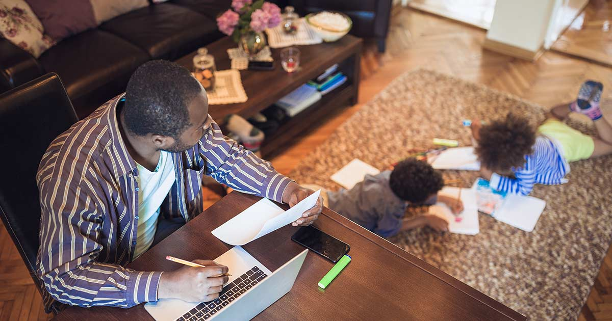 Father working from home while his children play on the floor