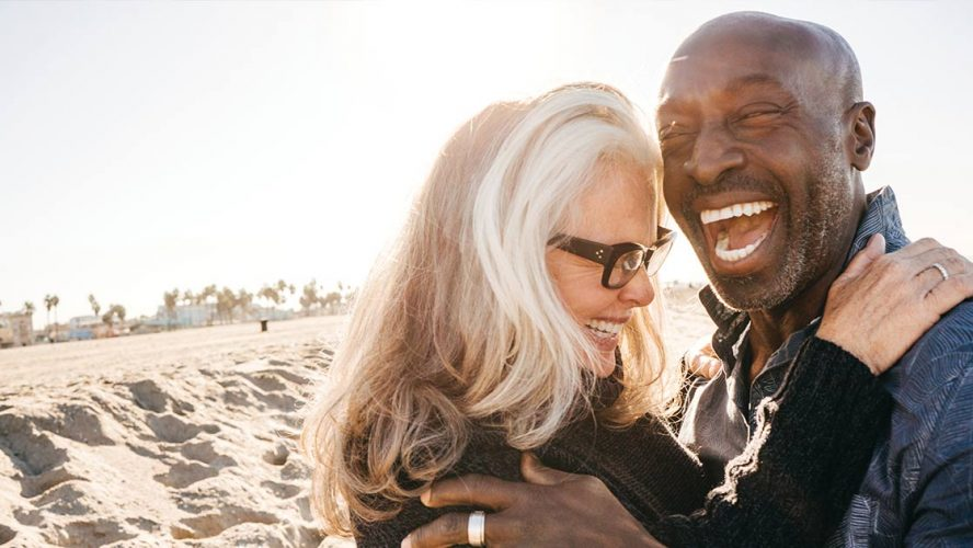 Mature couple laughing and hugging on a beach