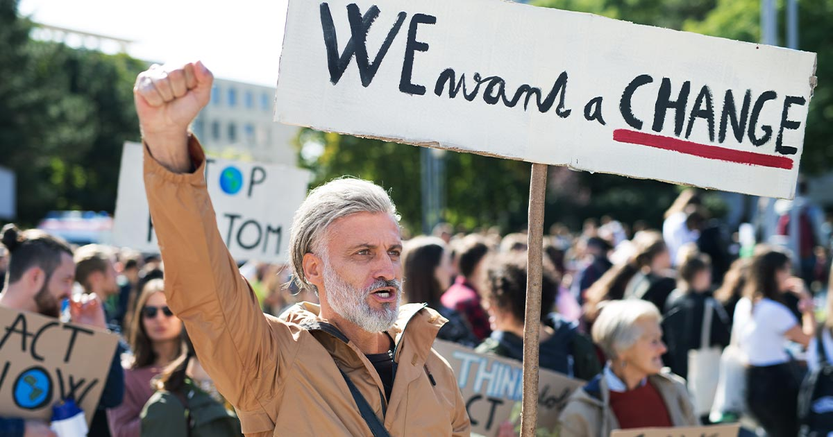 Grey-haired man marching in a protest