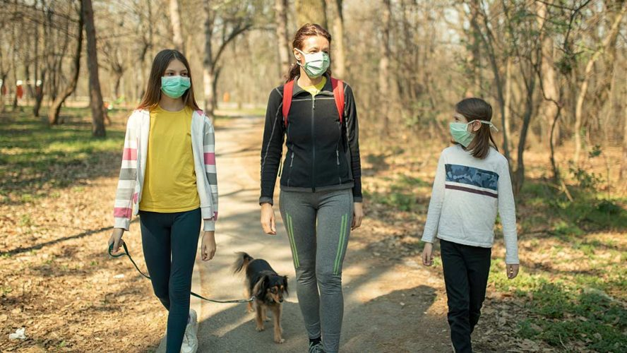 Mother and two daughters wearing medical face masks and hiking with their dog