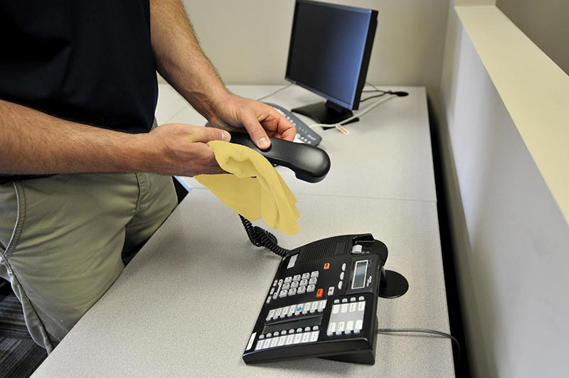 ServiceMaster Clean specialist disinfecting phone in an office
