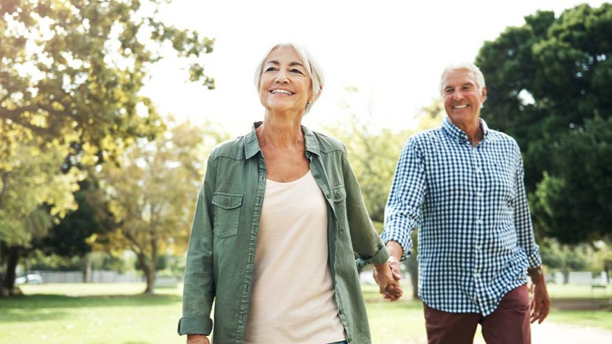 Two happy seniors walking in a park