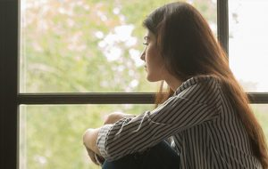 Woman sitting by a window and looking outside