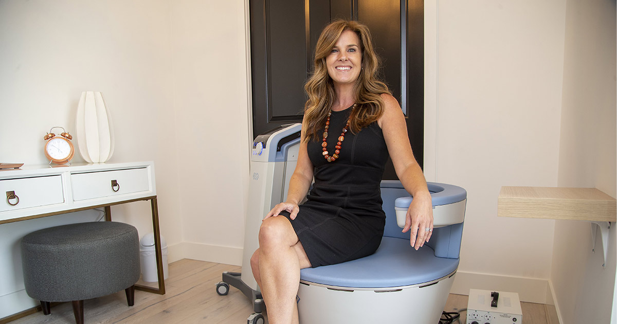 Erin Craven posing with a UROSPOT BTL EMSELLA Chair