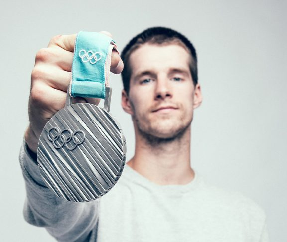 Max Parrot holding up his Olympic medal