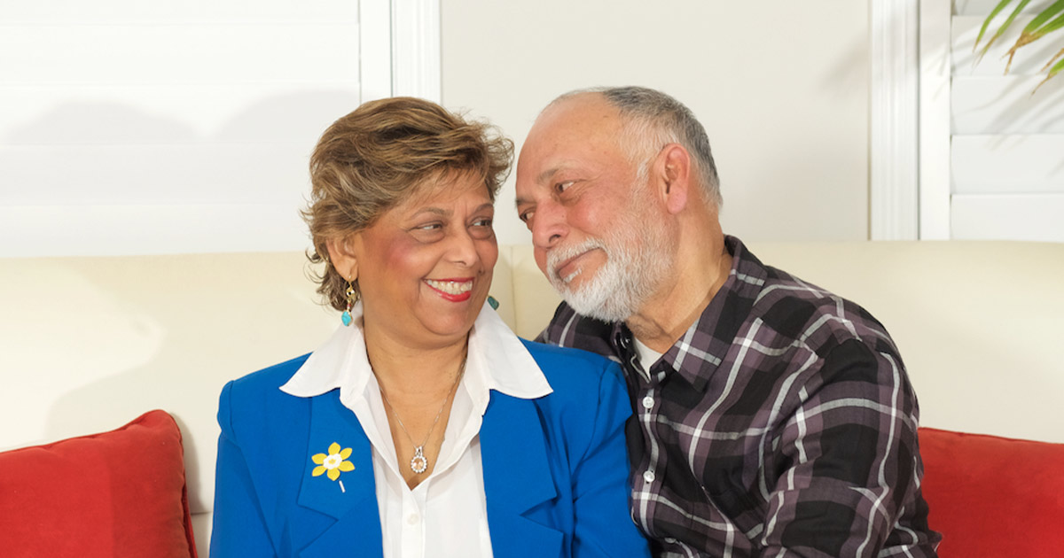 Two middle-aged people smiling at each other, one wears a CCS daffodil pin