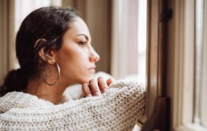 University student looking out of her window with a sad expression