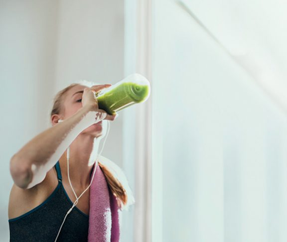 Woman drinking from a water bottle while working out