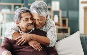 Elderly couple hugging in their home