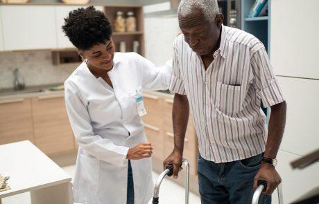 Health care worker helping elderly man use his walker