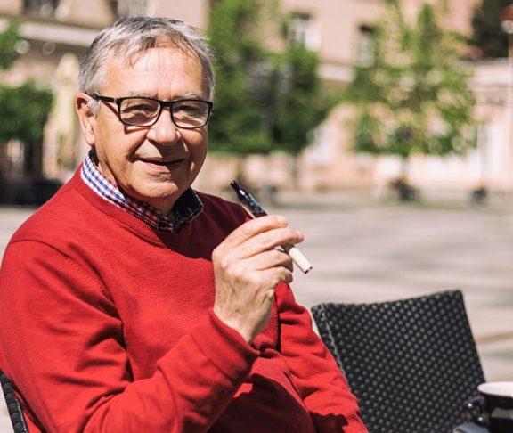 Senior man smoking an e-cigarette on a coffee shop patio