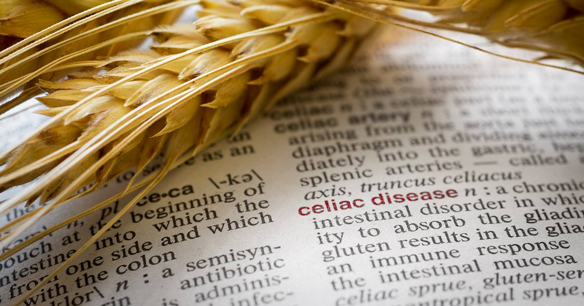 Wheat laid atop an open dictionary showing the definition of celiac disease