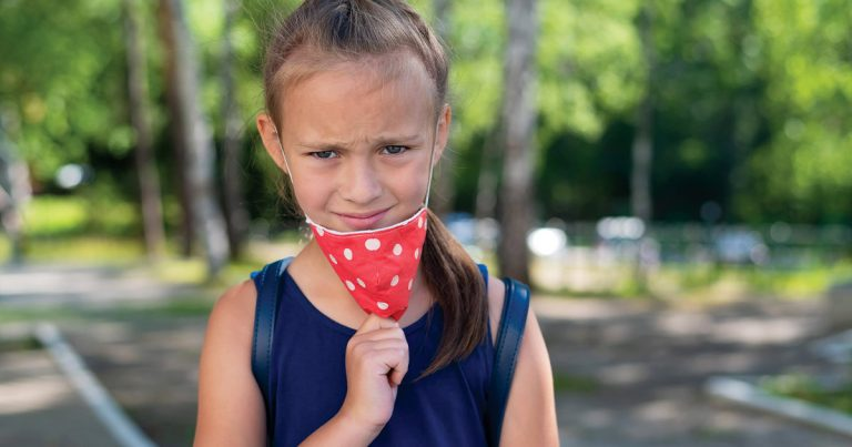 Young girl pulling down her COVID mask and raising her eyebrow at the viewer