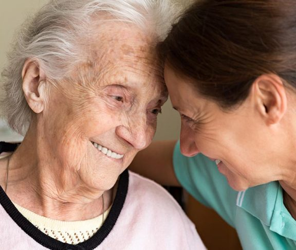Elderly woman and her daughter sharing an intimate moment