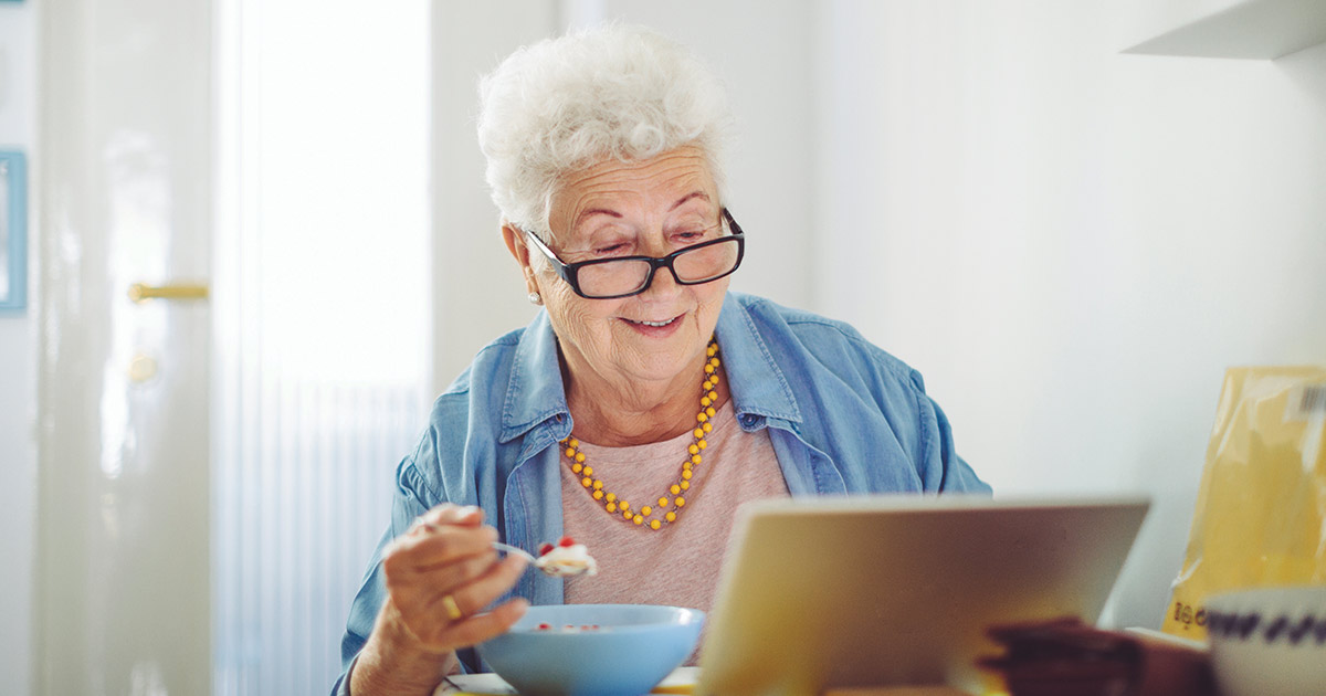 Elderly woman reading while eating a meal in her kitchen