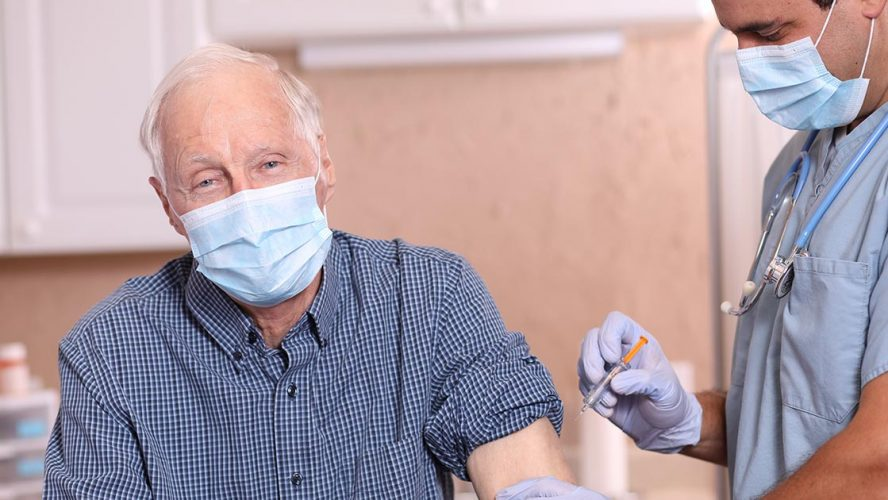 Senior man wearing face mask and receiving vaccination