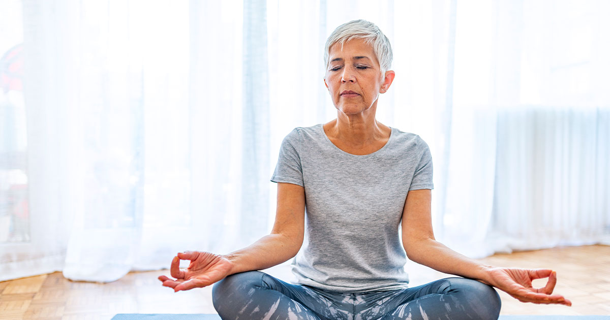 Senior woman doing yoga indoors