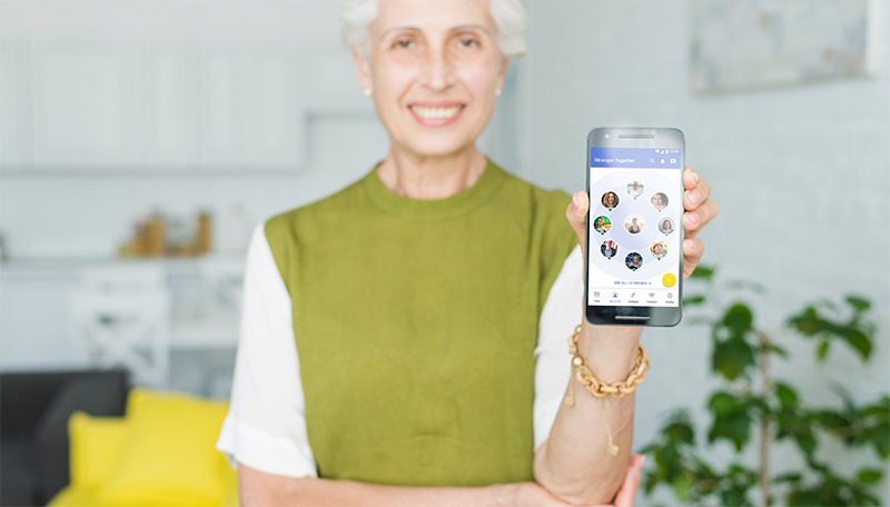 Senior woman holding up phone to show the Stronger Together app