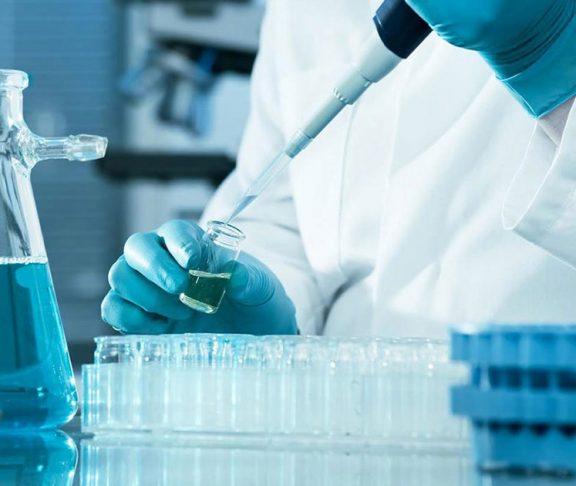 Scientist performing an experiment using vials of liquid