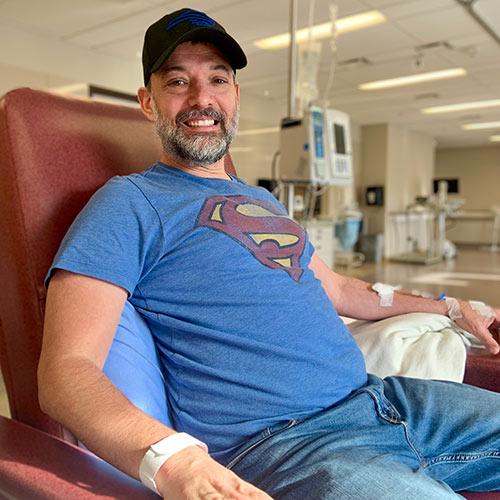 Steven Gallagher receiving a treatment while wearing a Superman t-shirt