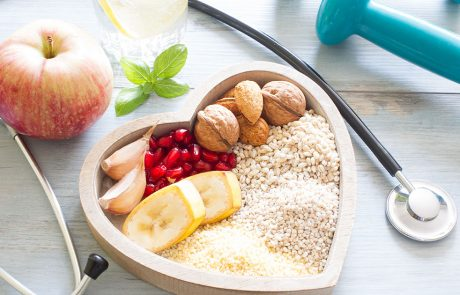 A bowl filled with nutrient rich foods placed in the middle of a stethoscope and dumbell