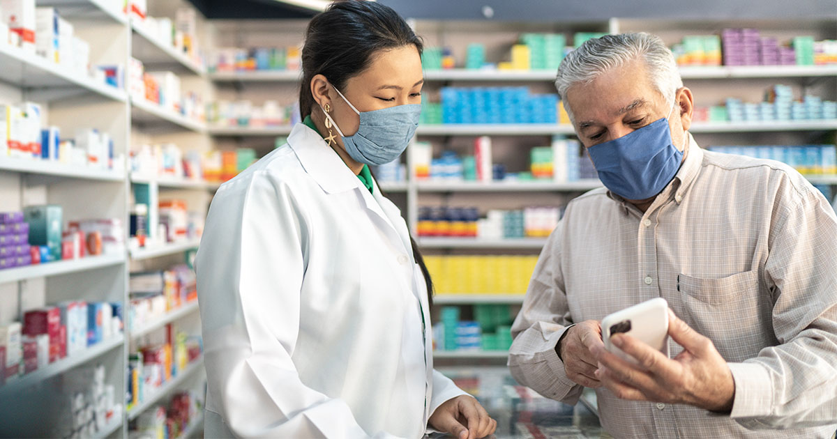Pharmacist with patient looking at phone