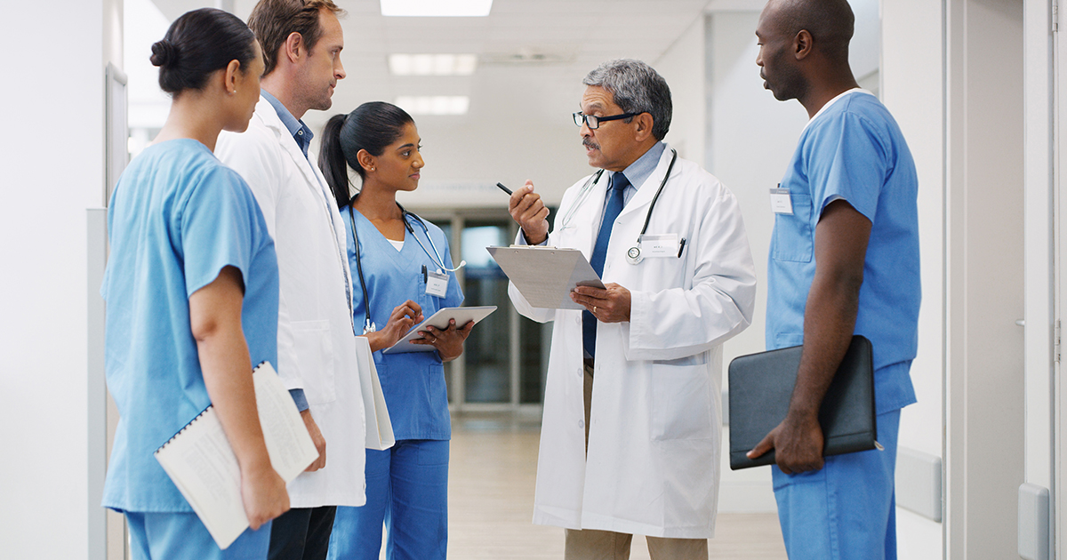Senior doctor talking to group of doctors in the hospital
