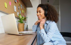 Woman-Listening-To-Headphones-On-Laptop