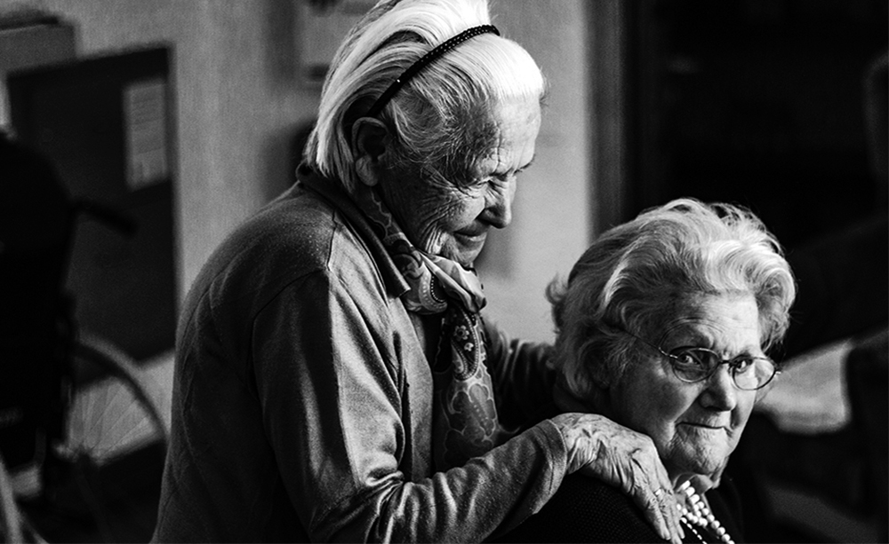 One elderly woman holding the shoulders of another
