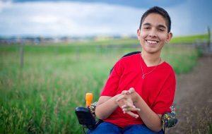 Ishan Manerikar, a smiling teenager in a wheelchair.