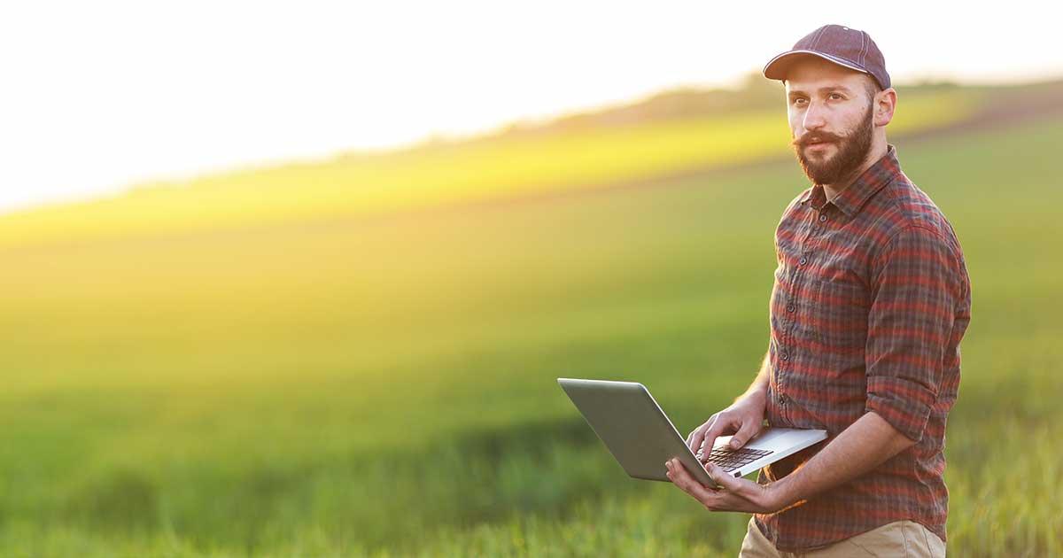 Farmer using laptop in a field