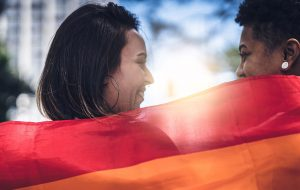 Two people smiling and holding up a rainbow Pride flag behind their shoulders.jpg