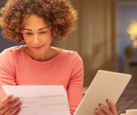 A woman comparing business reports at home