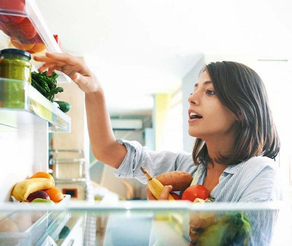 Woman choosing fresh food from her fridge