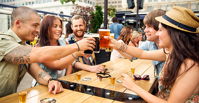 A group of people cheering their drinks on a patio