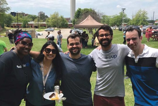Five smiling people at an outdoors event